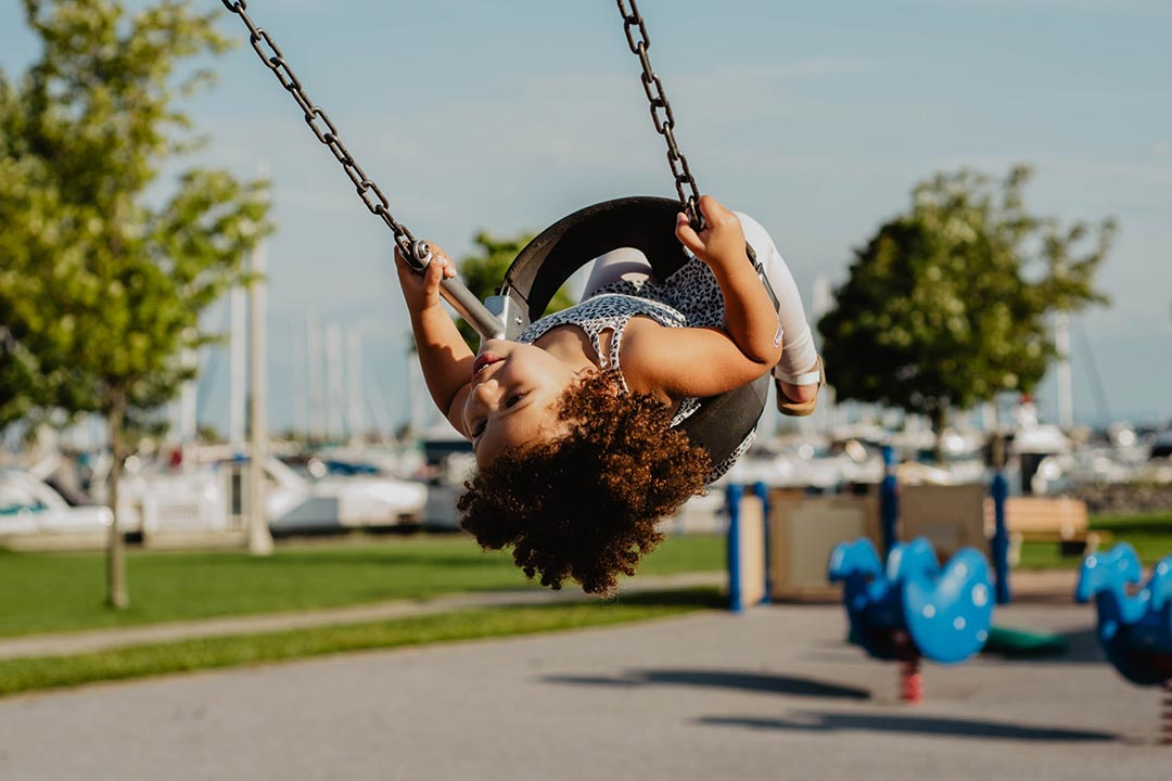 young girl swinging, looking back upside-down