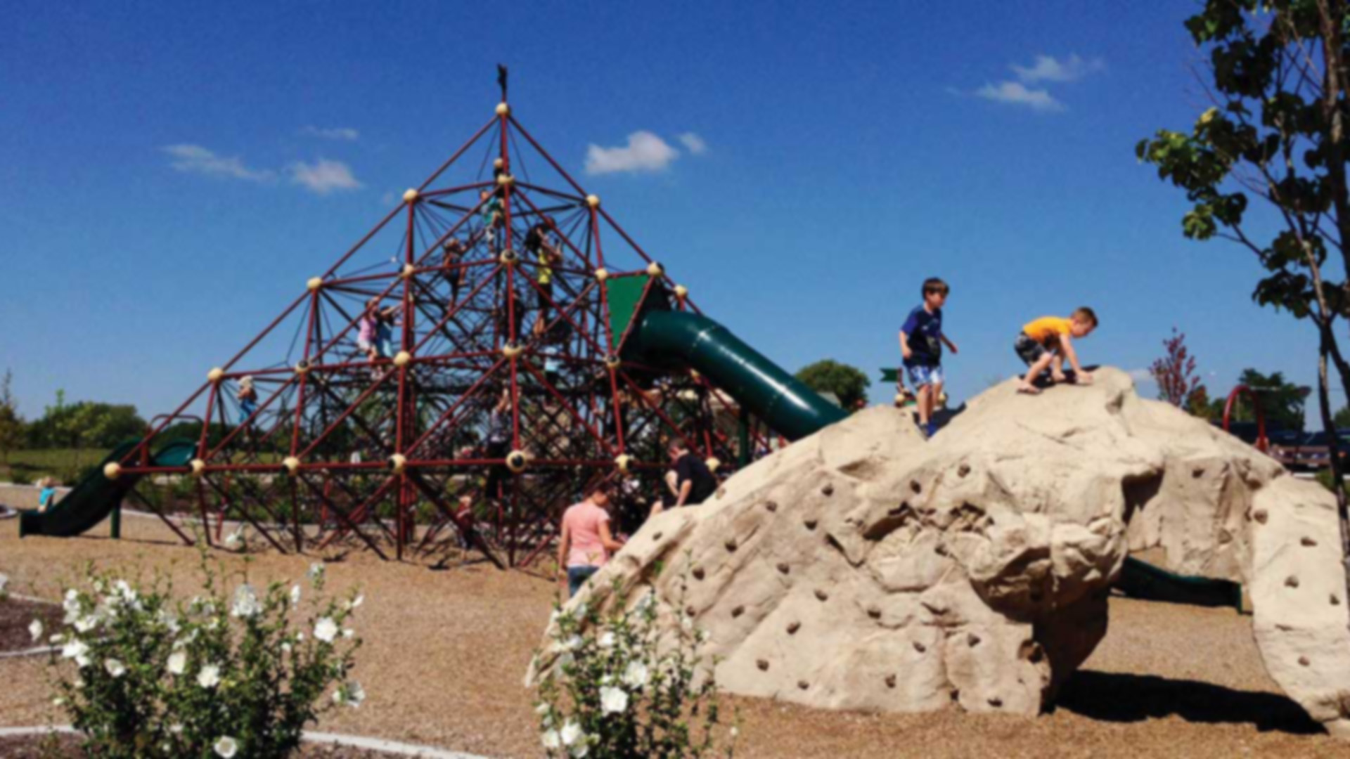 kids climbing on a rock sculpture and rope playground