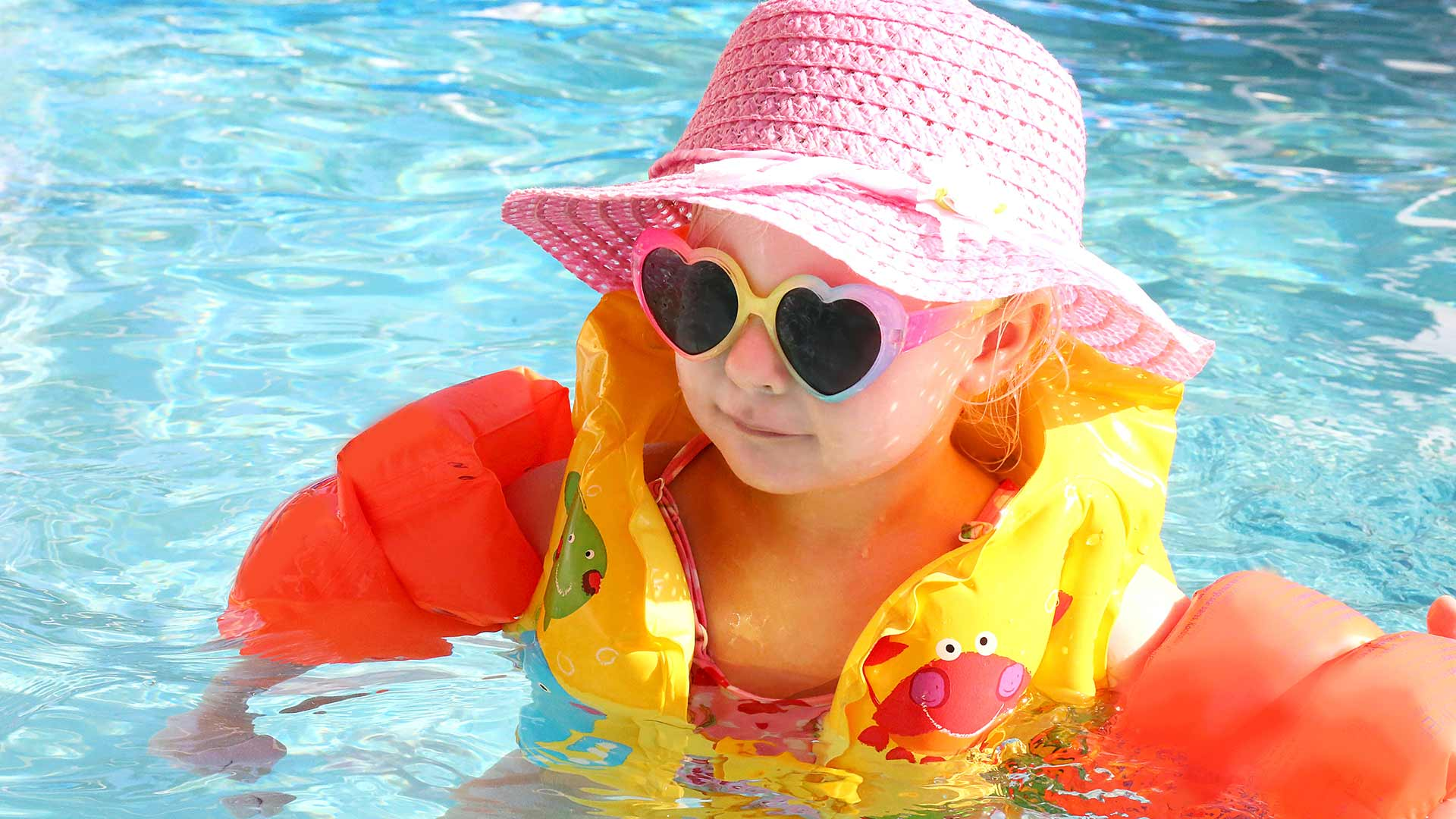 baby in pool with floaties and sun glasses