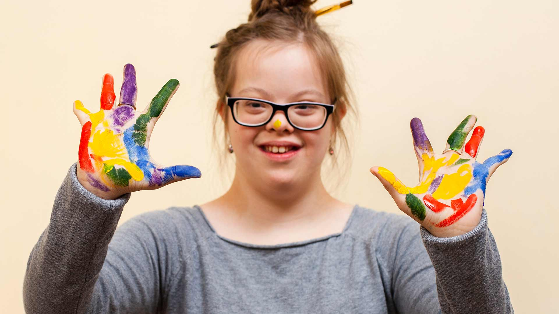 girl with down syndrome showing off her colorful palms