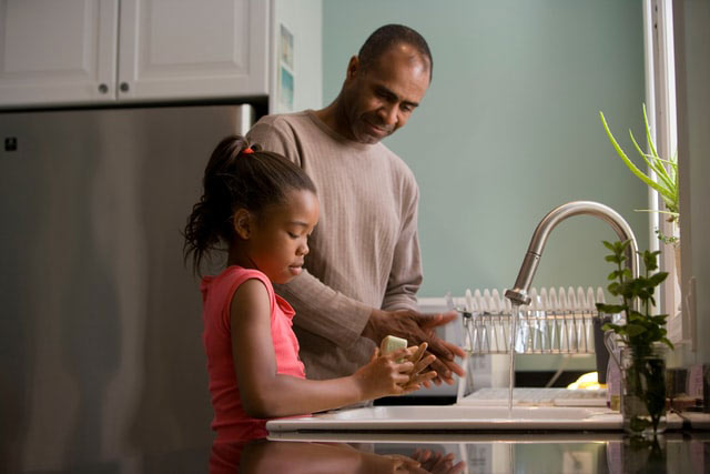 Father teaching daughter how to wash hands