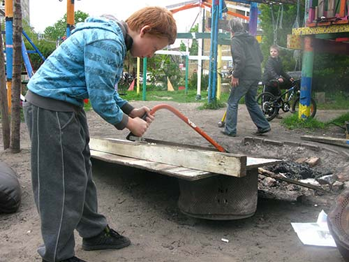 child sawing a post on adventure playground
