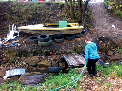 child with water hose crossing bridge to boat on dirt