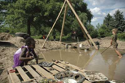 Children playing near home made pond