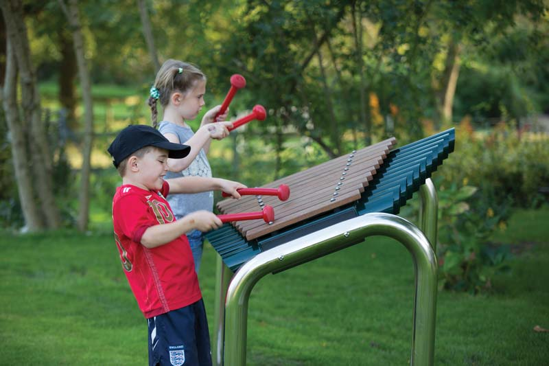 Kids playing on musical playground equipment