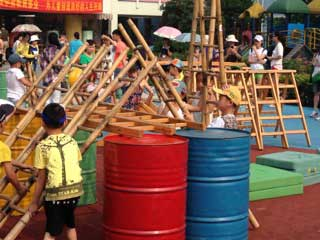 Kid with ladders and colorful barrels