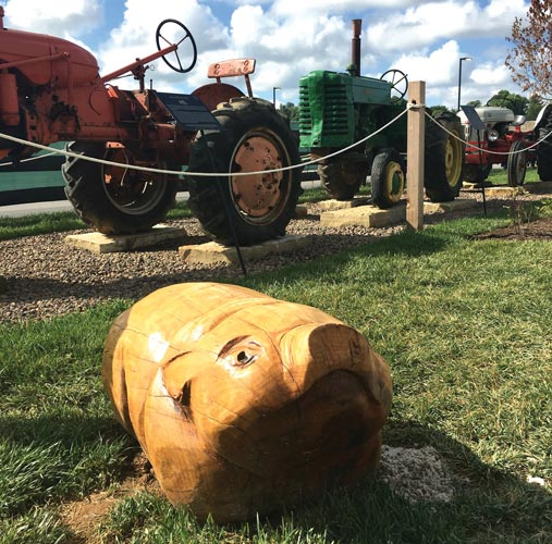 Pig carved out of wood and tractors
