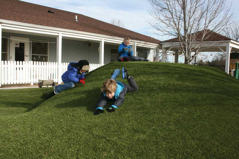Kids can safely romp and roll around on soft synthetic grass. Security Benefit child care facility, Topeka, KS.