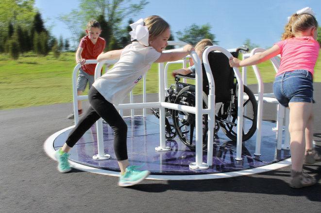 Children on a wheelchair accessible merry-go-round.