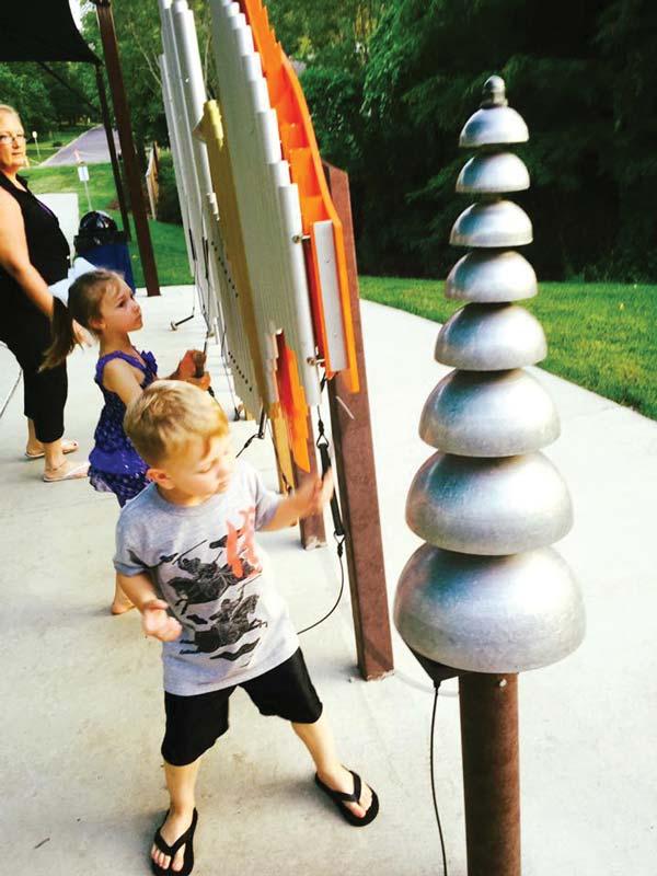 Kids playing on musical playground equipment