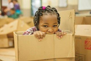 Girl playing in cardboard box