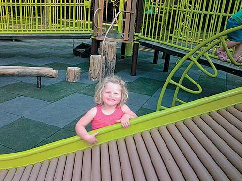 child standing near roller slide