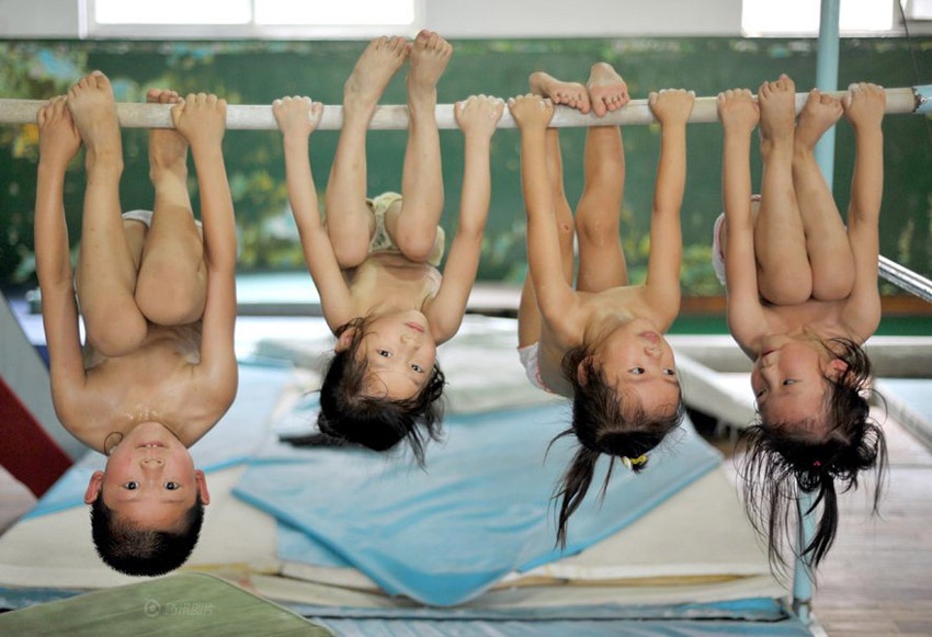 Toddlers hanging upside down from a bar