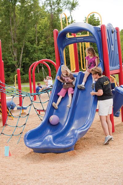 Girls sliding down slide with adult observing