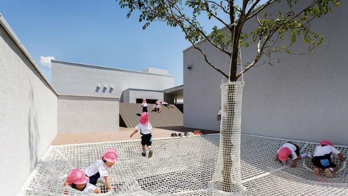 Children climb on nets in a nursery in Japan