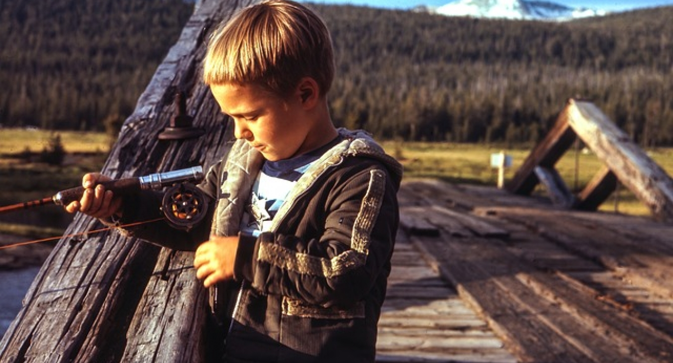 Boy fishing on a wooden bridge