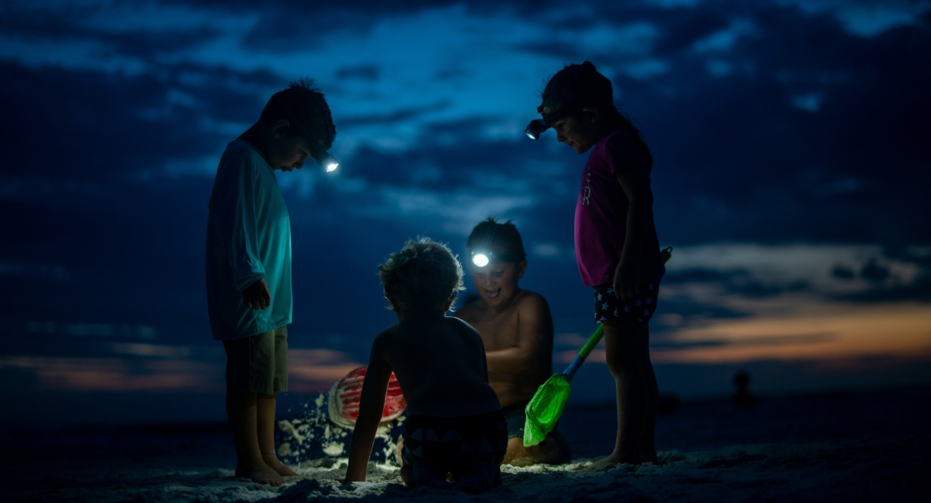 Kids playing on a beach at night