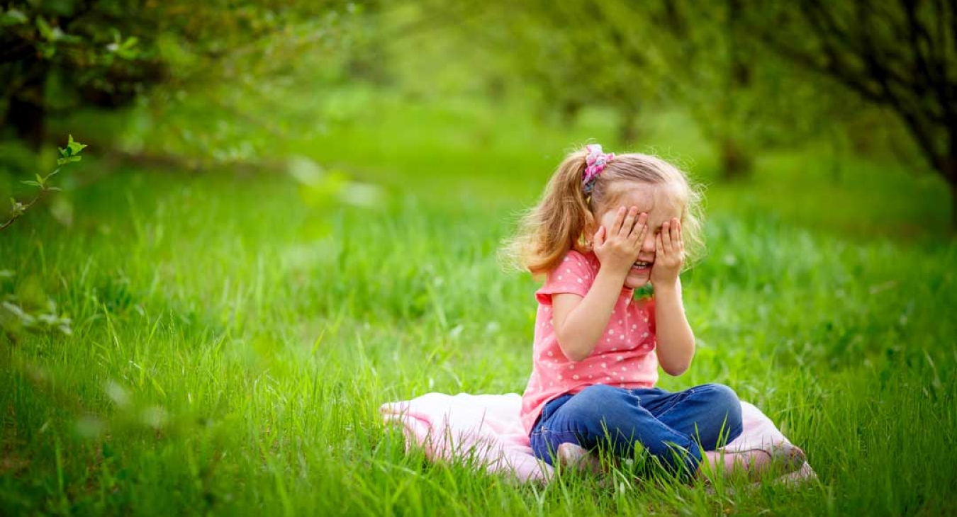 Young girl playing hid in seek in green grass