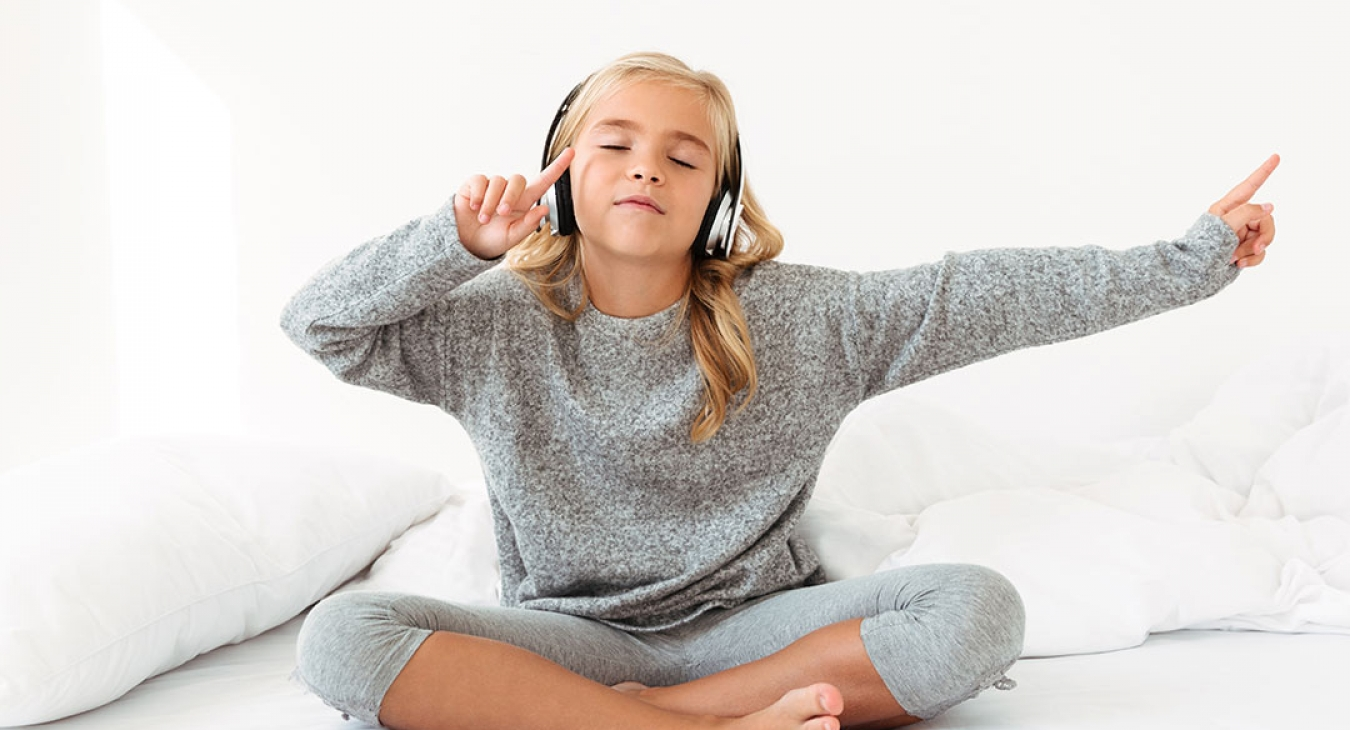 cute little blonde girl listening to music in her bed