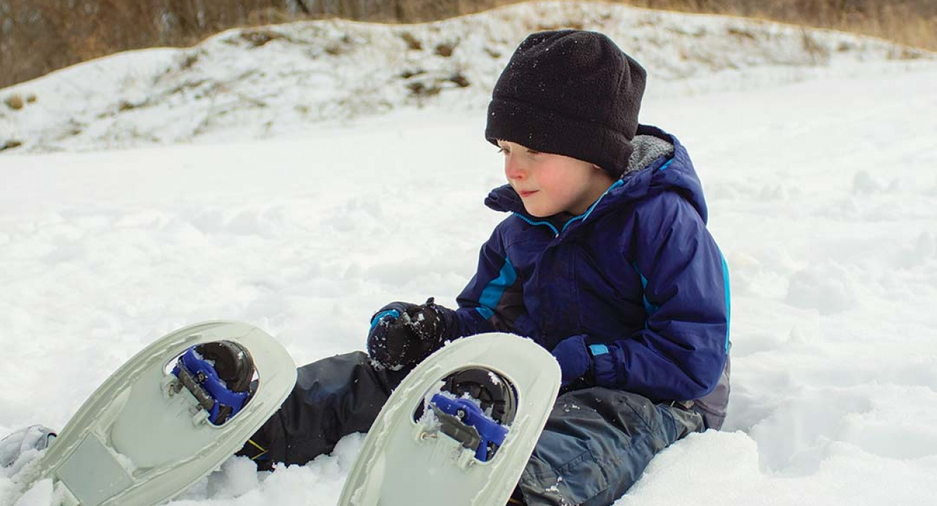 boy in snowshoes sitting in snow