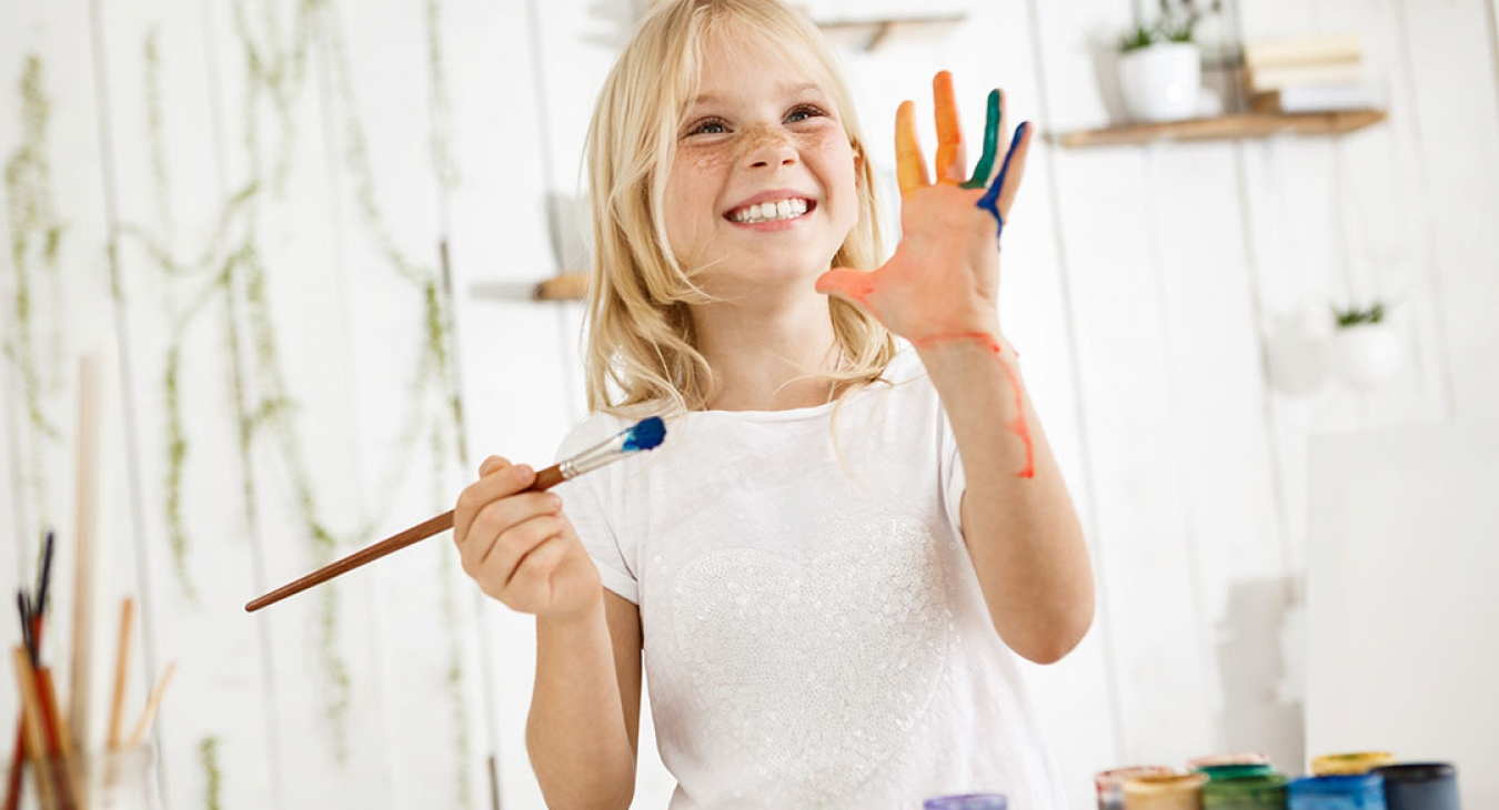 cute freckle faced blonde girl paints and makes a bit of a mess
