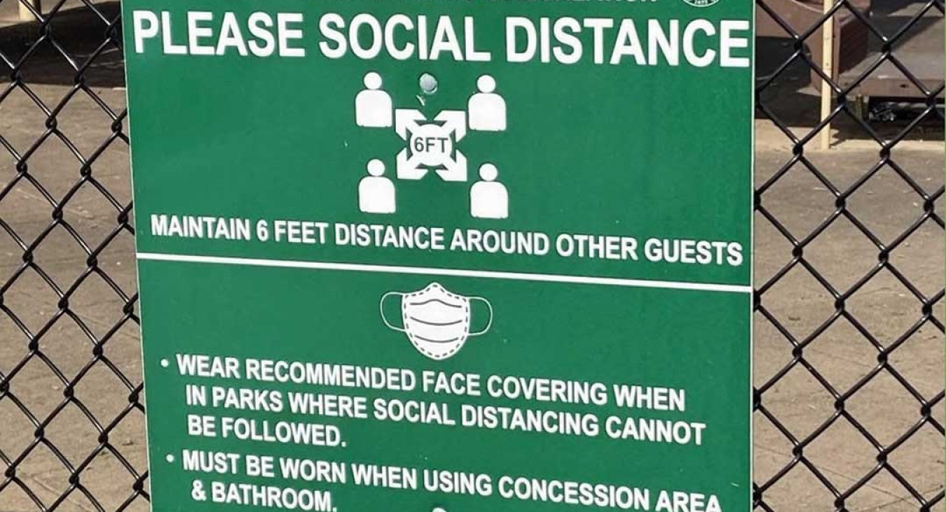 sign recommending social distancing and mask wearing