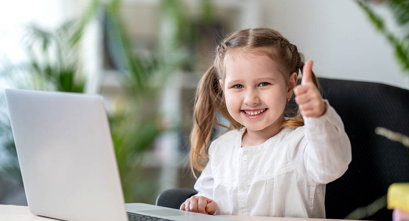Little girl going home school work on a laptop giving thumbs up