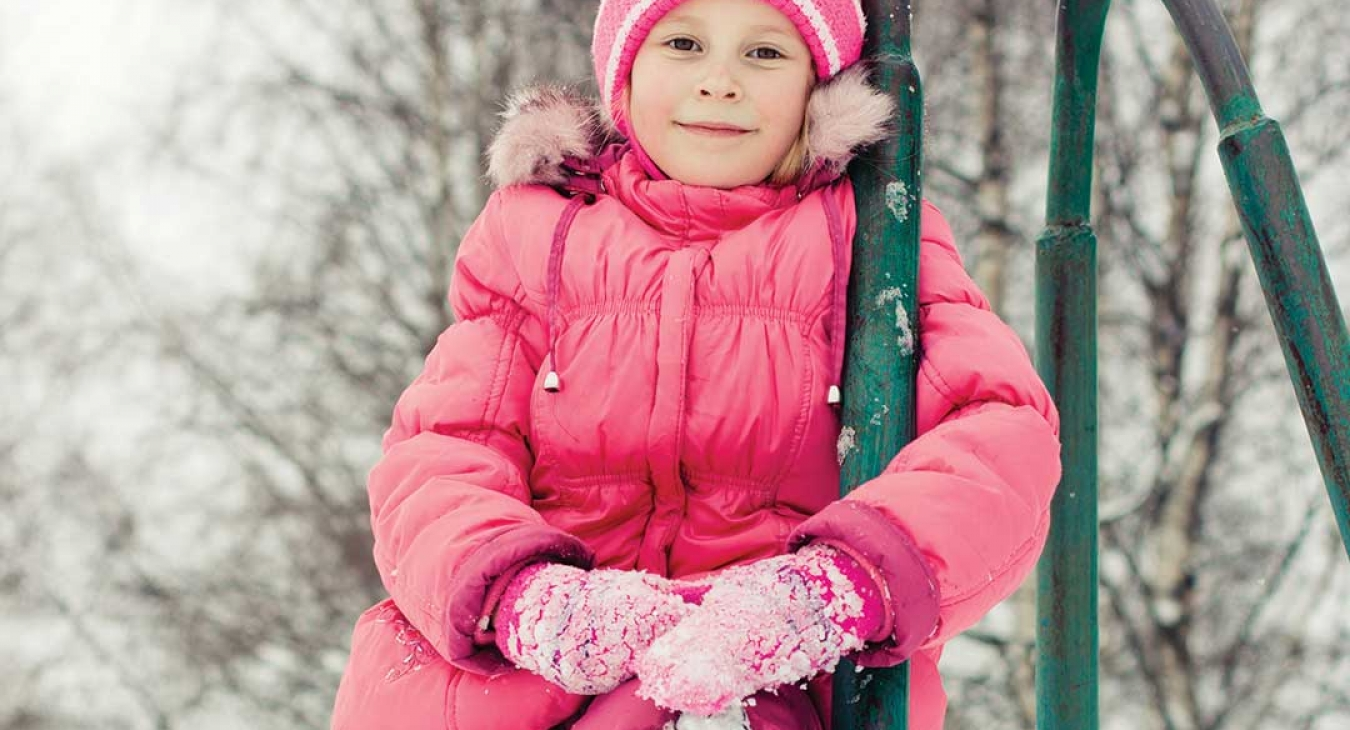 girl in snow clothes climbing on vintage playground