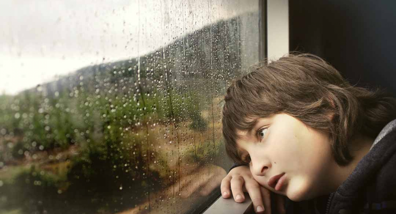 Child with ADHD looking outside on a rainy day