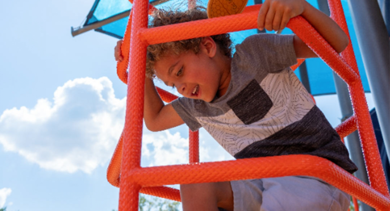 boy climbing on clean playground equipment