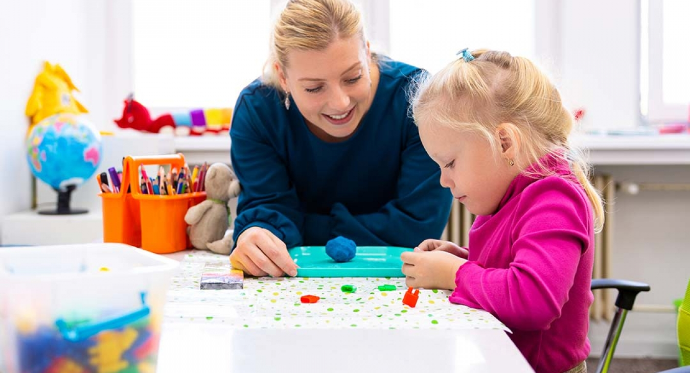 Therapist using games and play to help little blonde girl