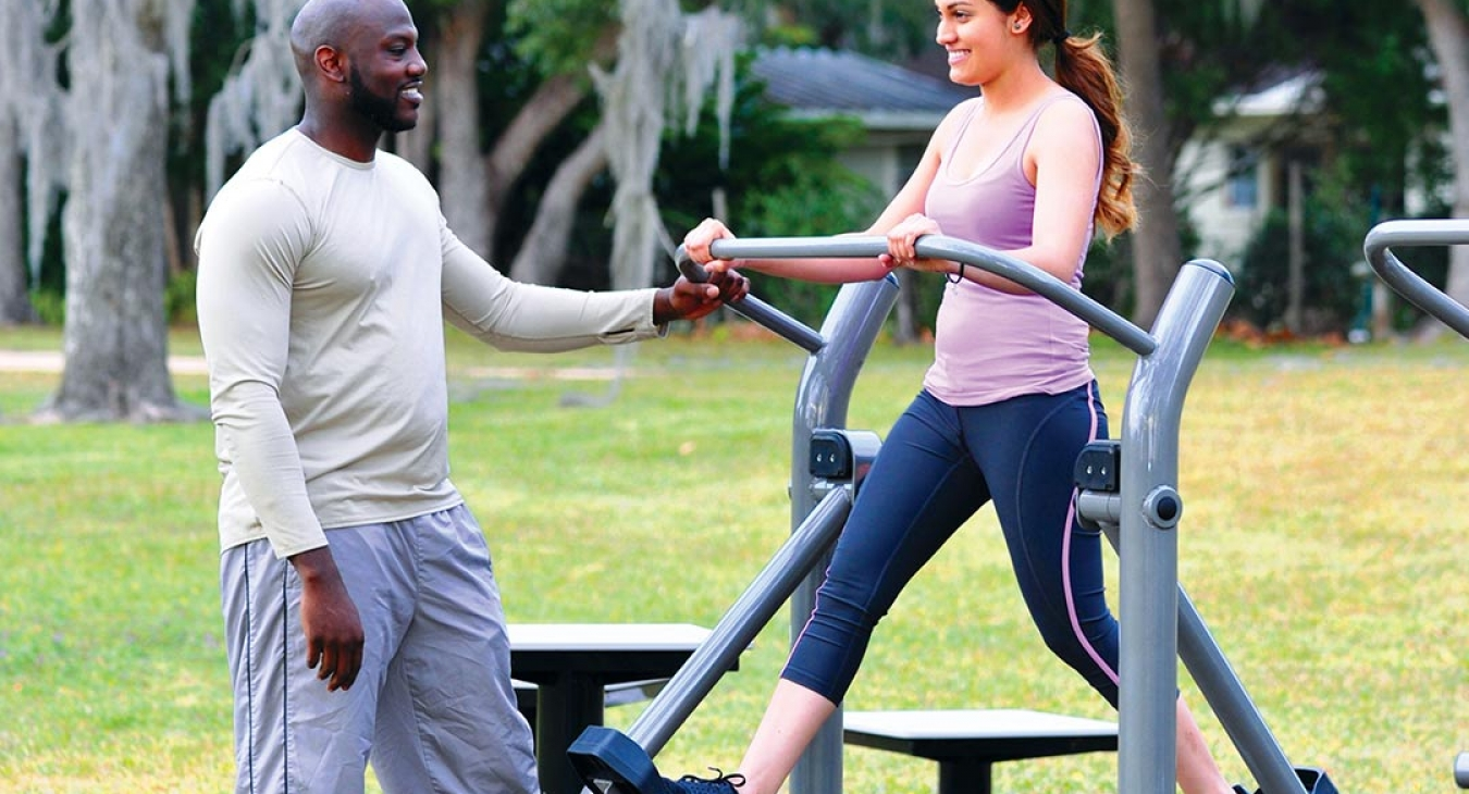 Couple working out on outdoor fitness equipment
