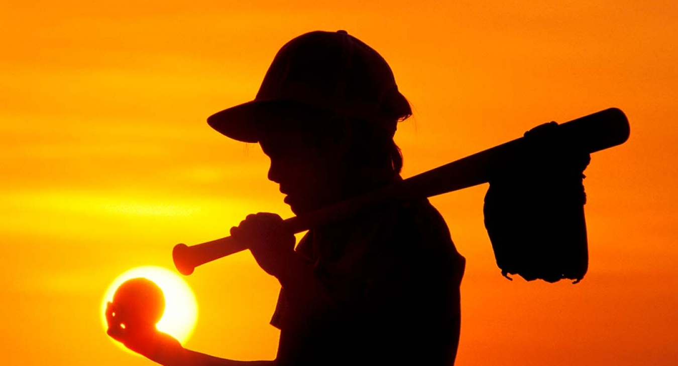 silhouette of boy with baseball equipment