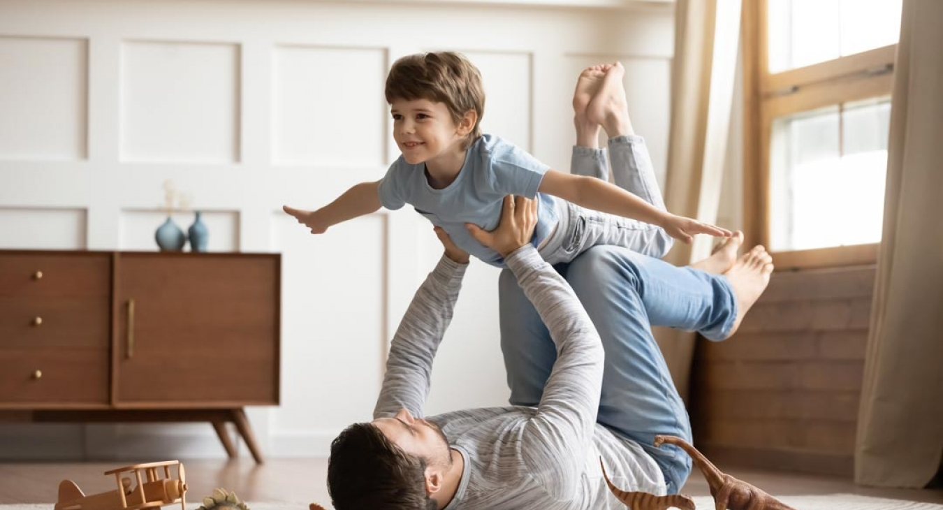 Dad playing airplane with son