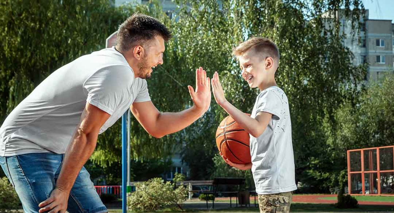 Father and son playing basketball together outdoor basketball court