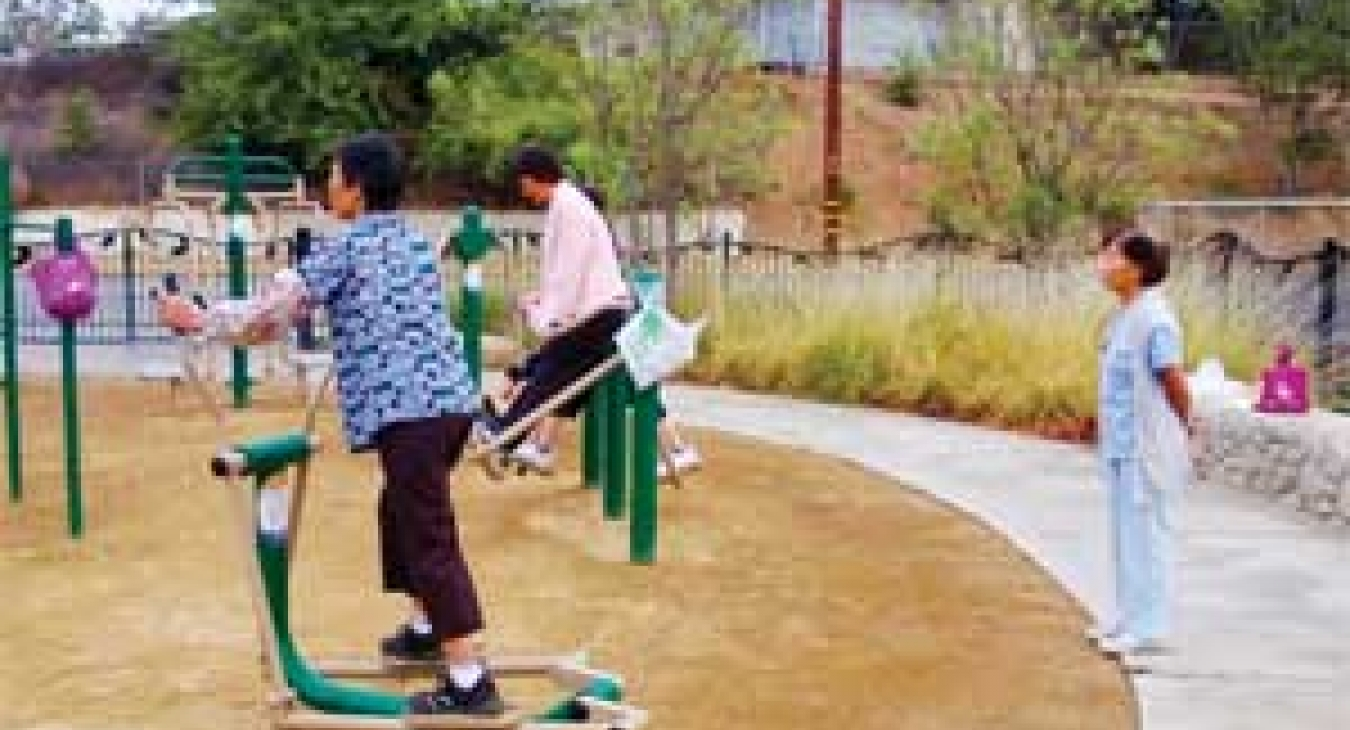 A parents gets in a workout at El Sereno Arroyo while children play
