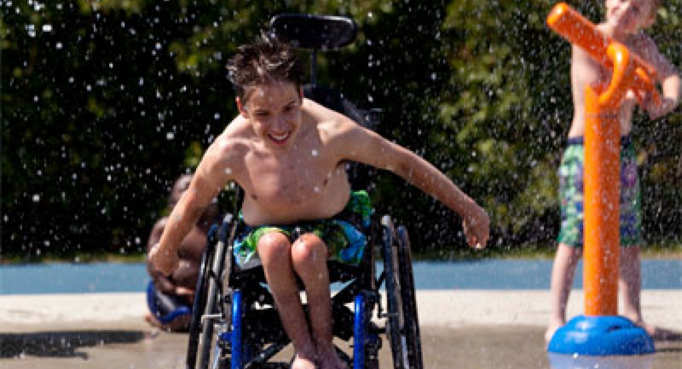 Boy in wheelchair enjoys a splash pad.
