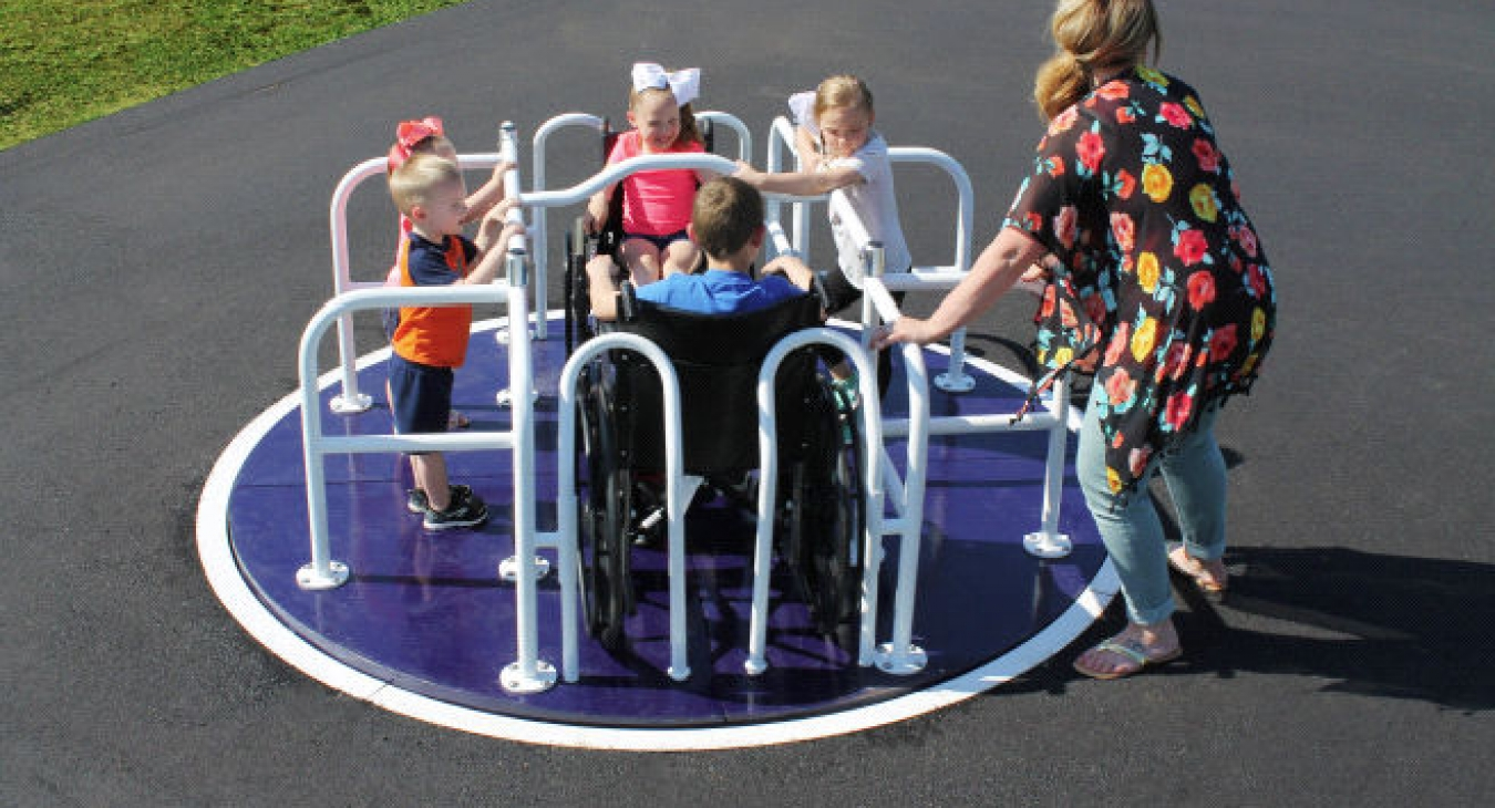 Children on a wheelchair accessible merry-go-round.