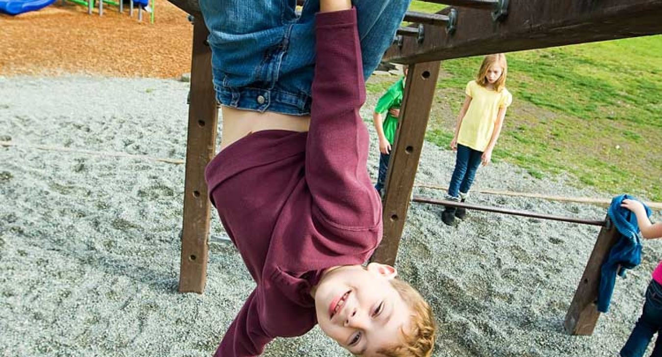 Child hanging from monkey bars.