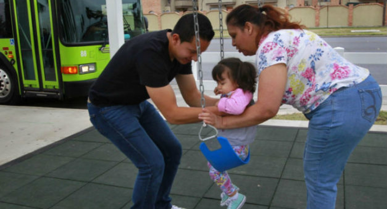 "Parents and a child use the Metro McAllen ""Swing and Rode"" bus stop."