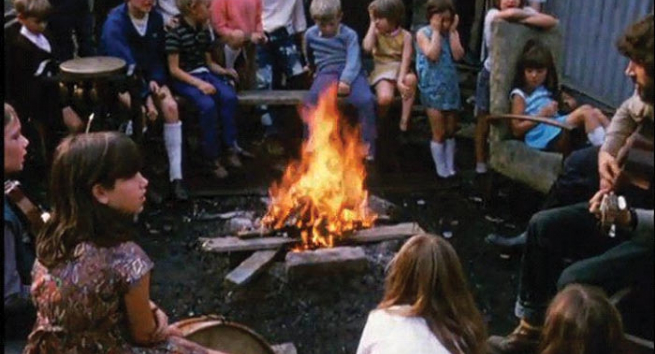 A Play worker hosting kids around a campfire.