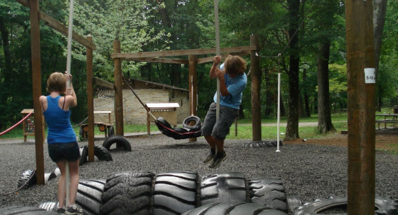 Teens playing on a playground made from old tires.