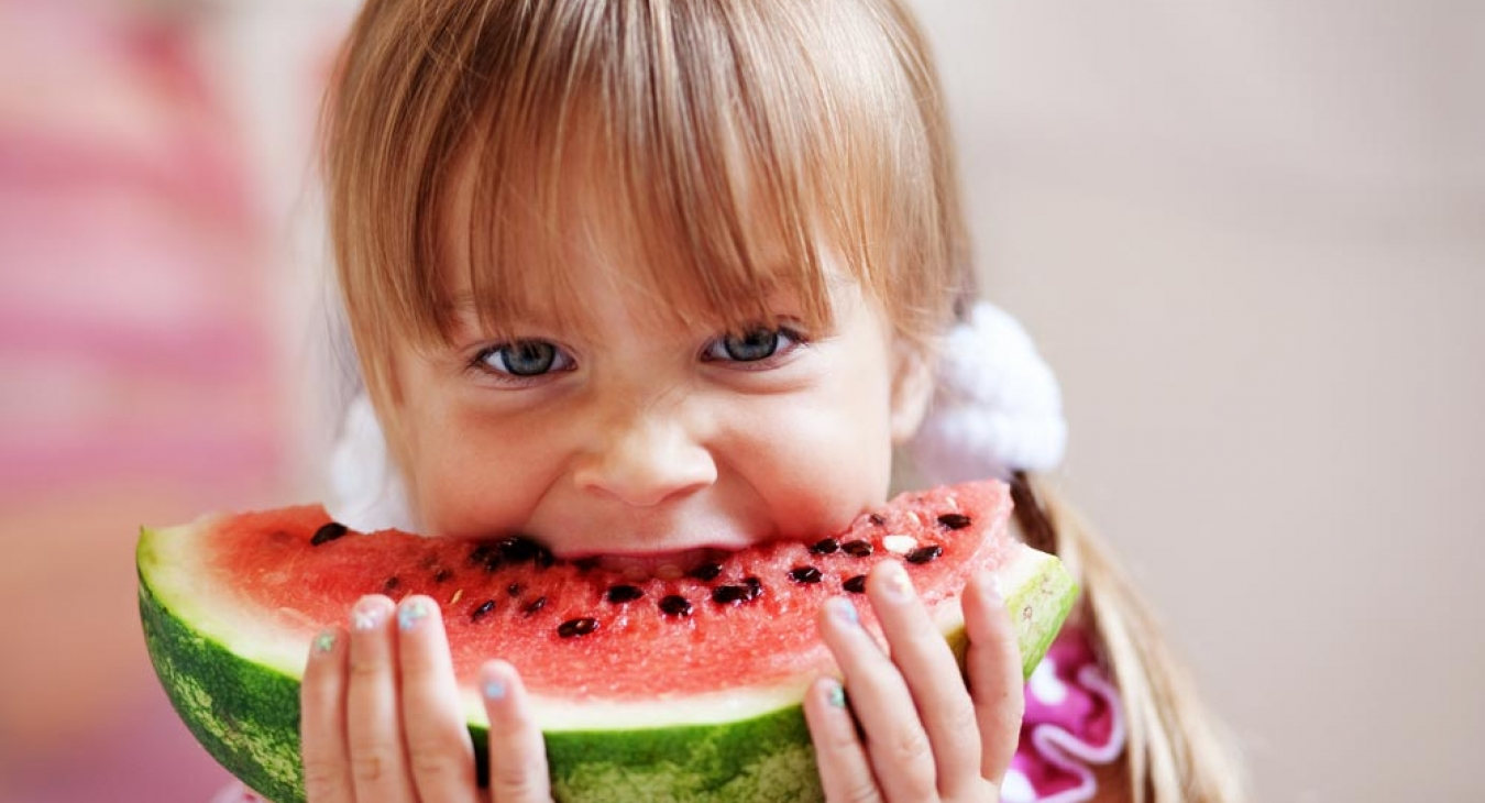 Young girl eating fruit at watermelon