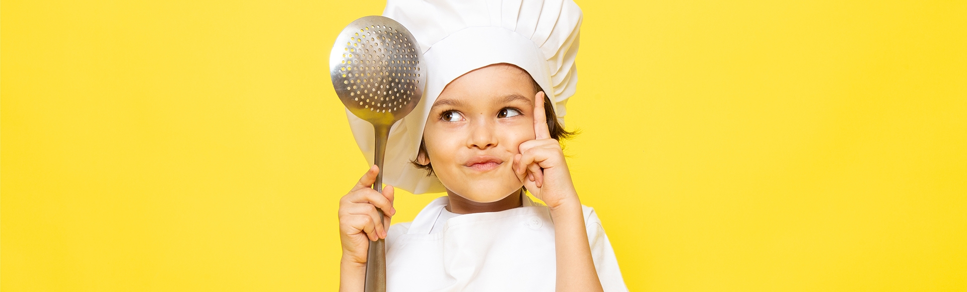 young boy wearing a chef's hat thinking about what to cook